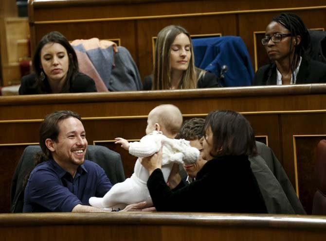 ATTENTION EDITORS: SPANISH LAW REQUIRES THAT THE FACES OF MINORS ARE MASKED IN PUBLICATIONS WITHIN SPAIN Podemos (We Can) party leader Pablo Iglesias (L) holds the infant son of fellow party deputy Carolina Bescansa (R) as parliament convened for the first time following a general election in Madrid, Spain, January 13, 2016.  REUTERS/Juan Medina
